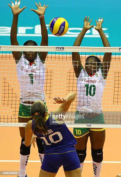 Fotso and Bikatal of Cameroon in action against Gabriela Guimaraes of Brazil during the 2014 FIVB Volleyball Women's World Championship Group B match...