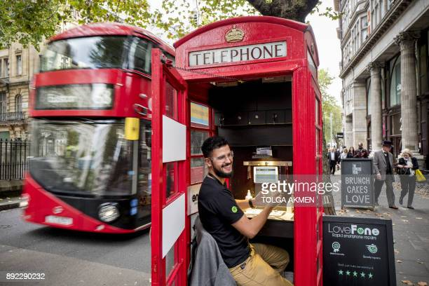 TOPSHOT Fouad Choaibi works inside a red telephone box from which he runs a smartphone repair shop on Southhampton Row in central London on October...