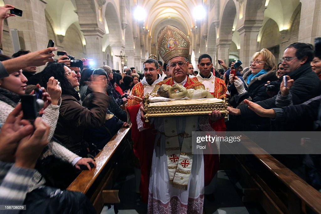 Foud Twal, the Latin Patriarch of the Holy Land, holds the Baby Jesus in Saint Catherine's Church at the end of the Christmas Midnight Mass and walks in procession to the 'Grotto', where Christians believe the Virgin Mary gave birth to Jesus Christ, in the adjacent Church of the Nativity on December 25, 2012 in Bethlehem, West Bank. Thousands of pilgrims made their way to the Church of the Nativity this week to worship at the sacred site believed to be the birthplace of Jesus.