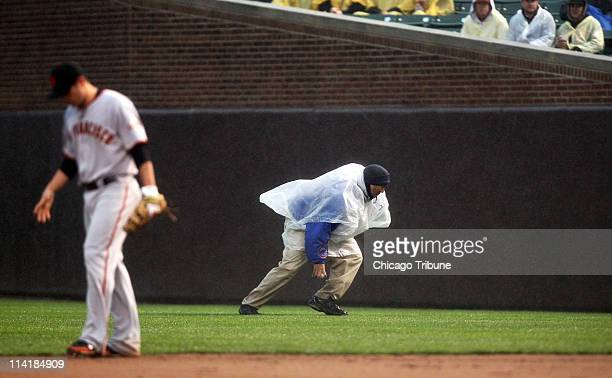 A foul ball is retrieved by a worker wearing a poncho during a rainy game between the Chicago Cubs and the San Francisco Giants at Wrigley Field in...