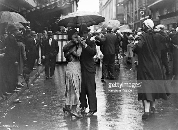 Foule de parisiens dansant dans la rue malgré les averses à Paris France le 14 juillet 1931