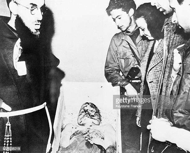 Foule défilant devant le corps de Mussolini qui a été pendu et placé dans un grand cercueil de sapin à Milan Italie en 1945