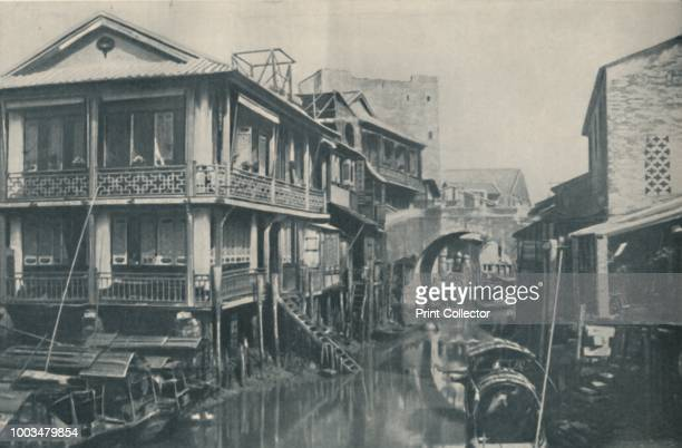 Fouled Waters Pass Beneath A Bridge That Leads To Unlovely Homes of Poverty and Pain', circa 1935. From Our Wonderful World, Volume III, edited by...