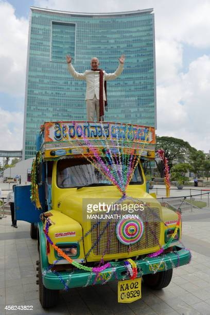 US founder and CEO of Amazoncom Jeff Bezos poses atop a lorry after handing over a two billion dollar cheque to Indian Vice President and Country...
