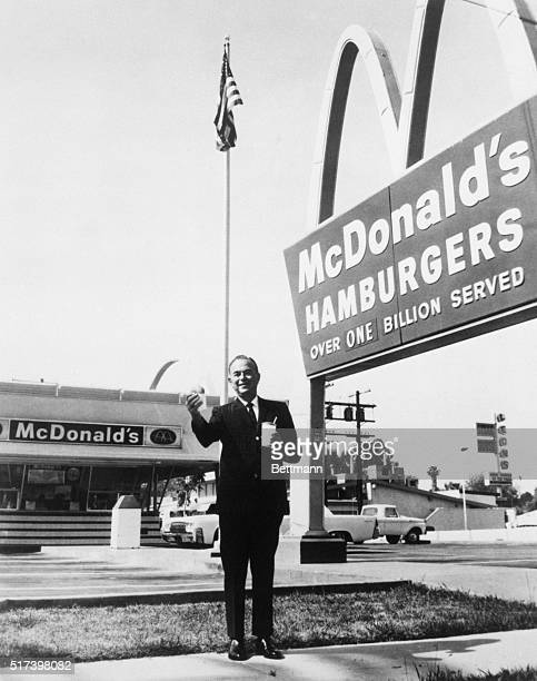 Founder and chairman of McDonald's Corporation Ray Kroc stands outside one of his franchises holding a hamburger and a drink