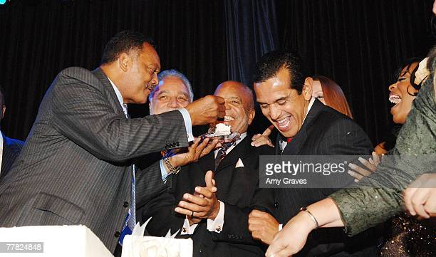 Founder and President of the Rainbow PUSH Coalition Reverend Jesse Jackson Sr feeds birthday cake to actress Founder of Motown Records Berry Gordy as...