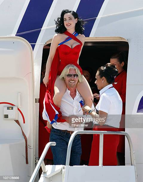 Founder and President of Virgin Group Sir Richard Branson carries burlesque artist Dita Von Teese on his shoulders as they board a Virgin Atlantic...