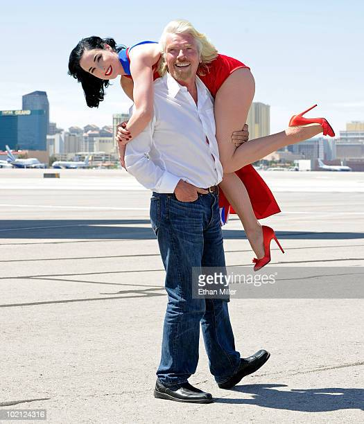 Founder and President of Virgin Group Sir Richard Branson holds burlesque artist Dita Von Teese on the tarmac at McCarran International Airport June...