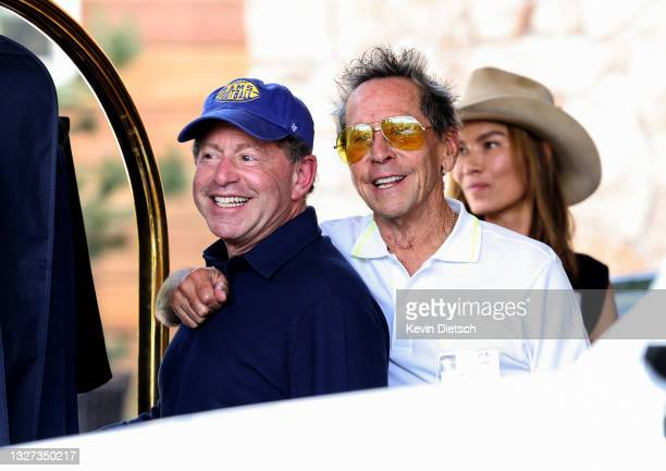 Founder of Imagine Entertainment Brian Grazer puts his arm around CEO of Activision Blizzard Bobby Kotick as they arrive for the Allen & Company Sun...