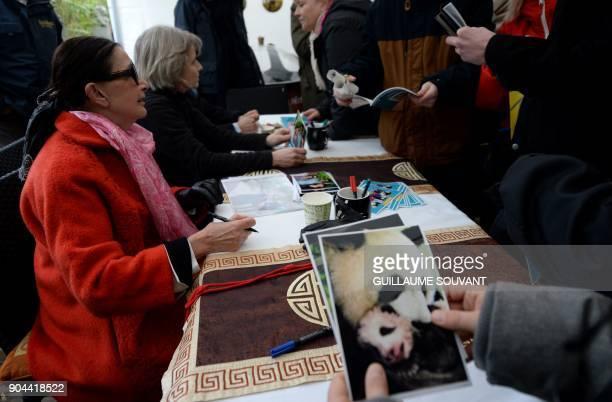 Founder of the Beauval zoo Francoise Delord signs photos of the Panda cub Yuan Meng and its mother Huan Huan during the cub's first public appearance...