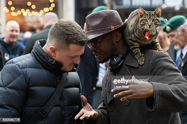 Founder of the English Defence League Tommy Robinson talks to a man with a cat outside the High Court as the bail hearing for marine Alexander...