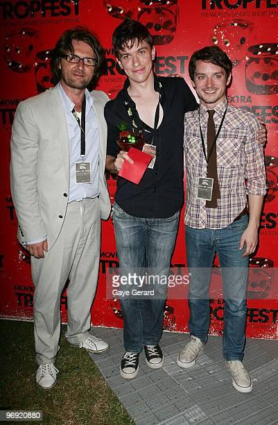 Founder of Tropfest John Polson Abe Forsythe winner of 1st prize for 'Shock' and actor Elijah Wood pose together during the Tropfest 2010 short film...
