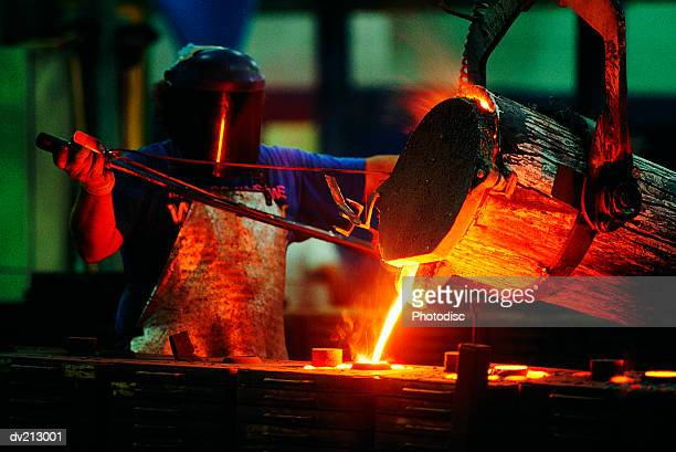 foundry worker pouring steel - blacksmith shop stock photos and pictures