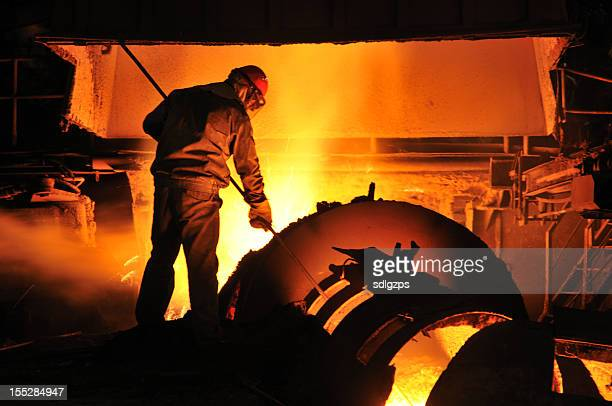 Foundry worker shoveling molten metal in a furnace