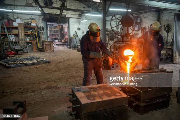 Foundry workers pour molten iron into moulds at the Barr and Grosvenor foundry on October 13, 2021 in Wolverhampton, England. Craftsmen at Barr and...