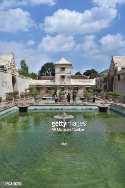 fountain against buildings in city - kraton stock pictures, royalty-free photos & images