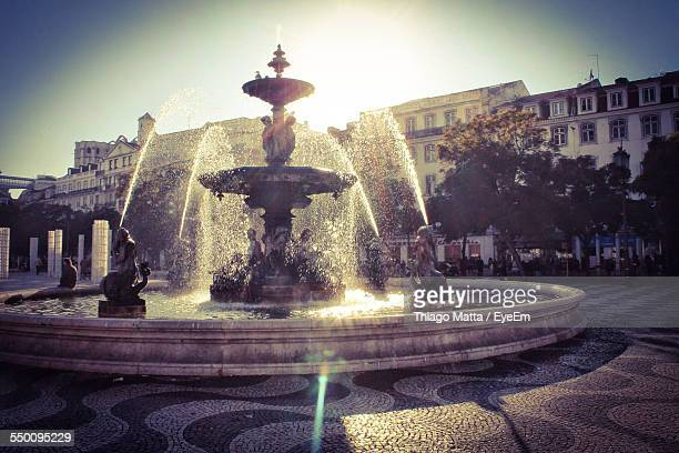 fountain against buildings in city - fountain stock pictures, royalty-free photos & images