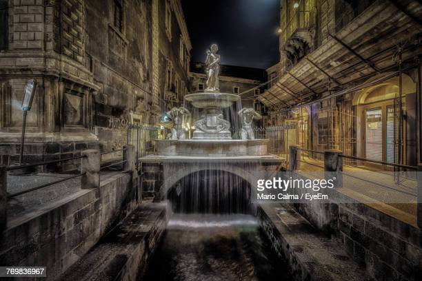 fountain amidst building at night - catania stock photos and pictures