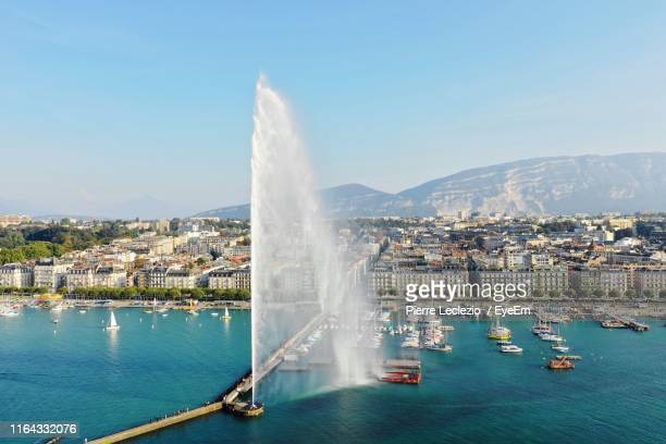 fountain amidst lake in city - geneva switzerland stock pictures, royalty-free photos & images