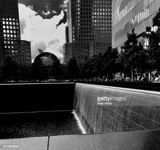 fountain at 911 memorial with world financial center and cloudy sky. black and white - 911 remembrance stock pictures, royalty-free photos & images