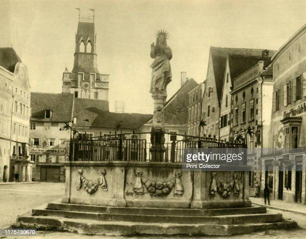 Fountain Braunau am Inn Upper Austria circa 1935 View of the town centre and the Fischbrunnen with clock tower behind The town of Braunau later...