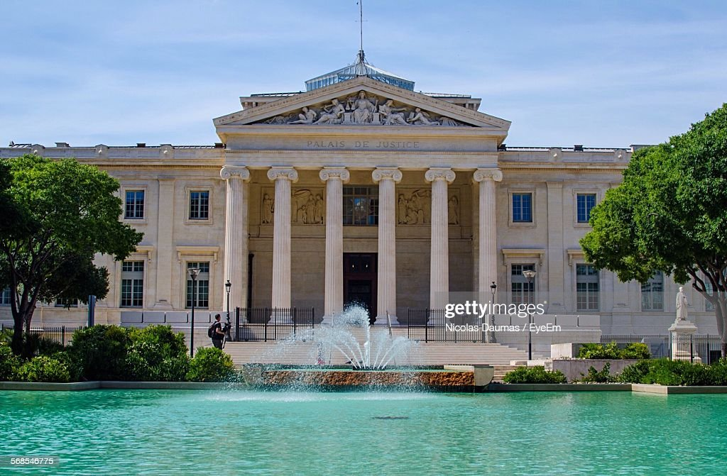 Fountain By Government Building Against Cloudy Sky : Stock Photo