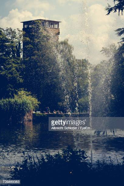 fountain by lake - albrecht schlotter stock photos and pictures