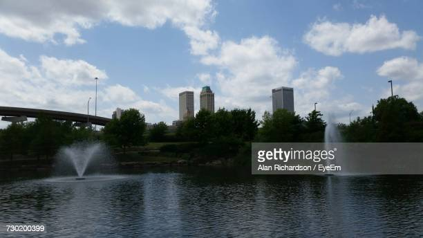 fountain in city against sky - tulsa stock pictures, royalty-free photos & images