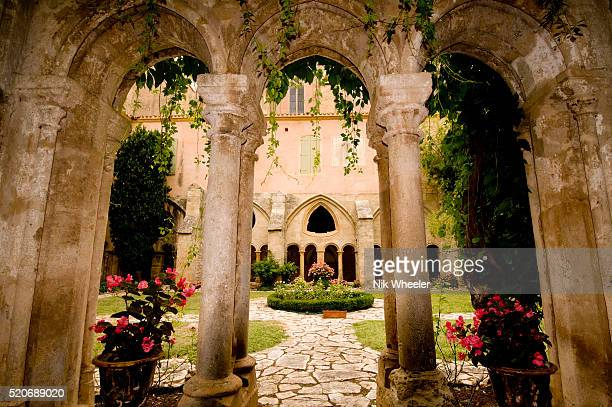 fountain in cloisters of abbey of valmagne, languedoc-roussillon, france - pezenas stock photos and pictures