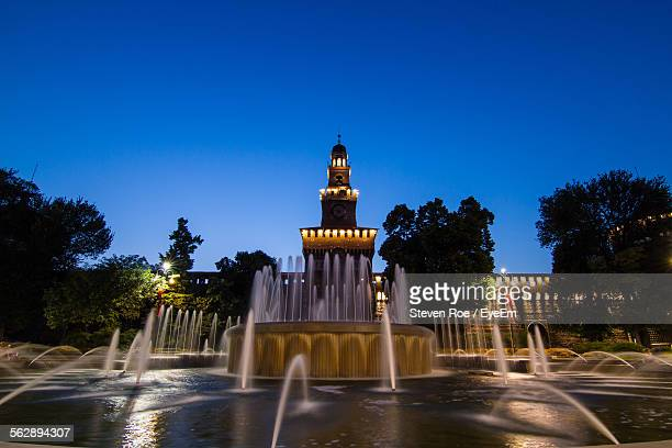 Fountain In Front Of Historic Building Against Clear Blue Sky At Night