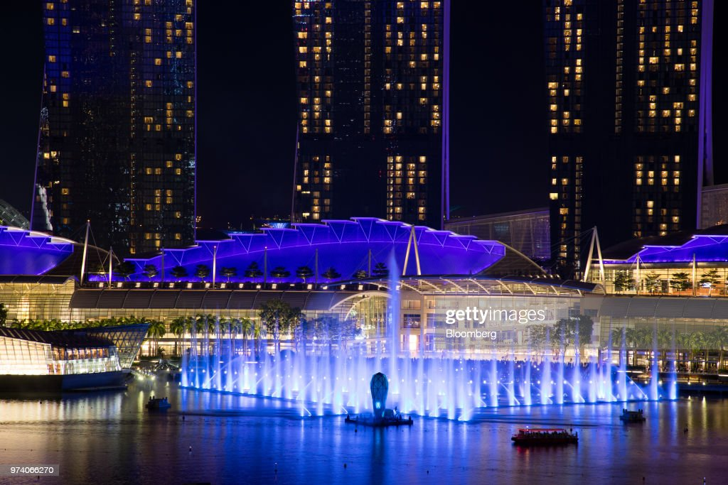 A fountain in front of the Marina Bay Sands hotel and casino is illuminated at night in Singapore, on Wednesday, June 13, 2018. Tourism as well as the consumer sector will likely see a lift thanks to the influx of international media at the recent DPRK-USA Summit, according to RHB Research Institute Singapore Pte. Photographer: SeongJoon Cho/Bloomberg via Getty Images