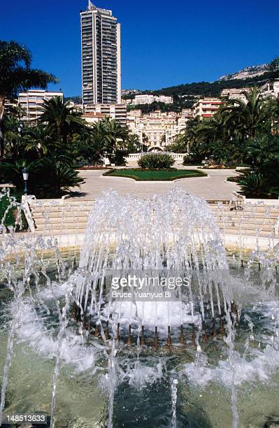 fountain in garden near place du casino with monte carlo's cityscape in background. - monte carlo stock pictures, royalty-free photos & images