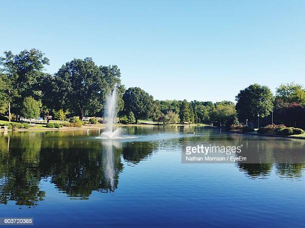 Fountain In Lake At Park Against Clear Sky