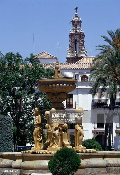 Fountain in Main Square, with the bell tower of St John's Church in the background, Ecija, Andalusia, Spain.