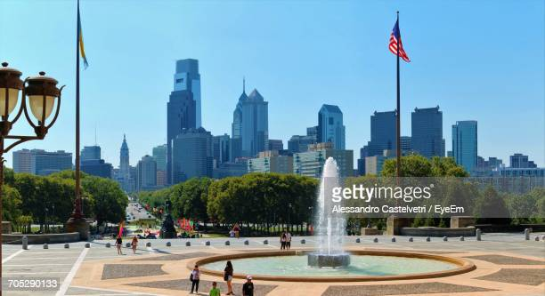 Fountain In Park With City In Background
