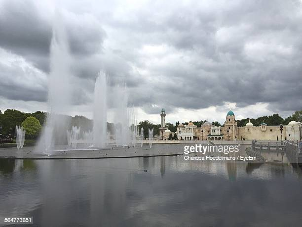 Fountain In River By Palace At Efteling Against Cloudy Sky