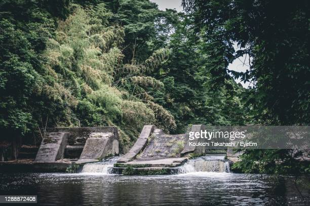 fountain in swimming pool by river against sky - koukichi stock pictures, royalty-free photos & images