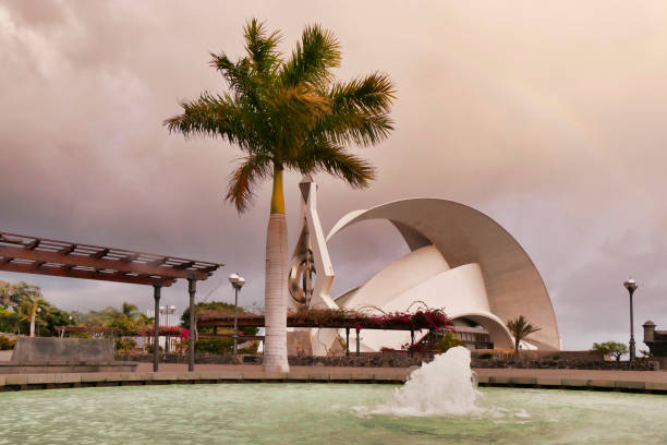 A fountain of the Parque Maritimo with a wind sculpture by Cesar Manrique and the Auditorium designed by Santiago Calatrava in the background.