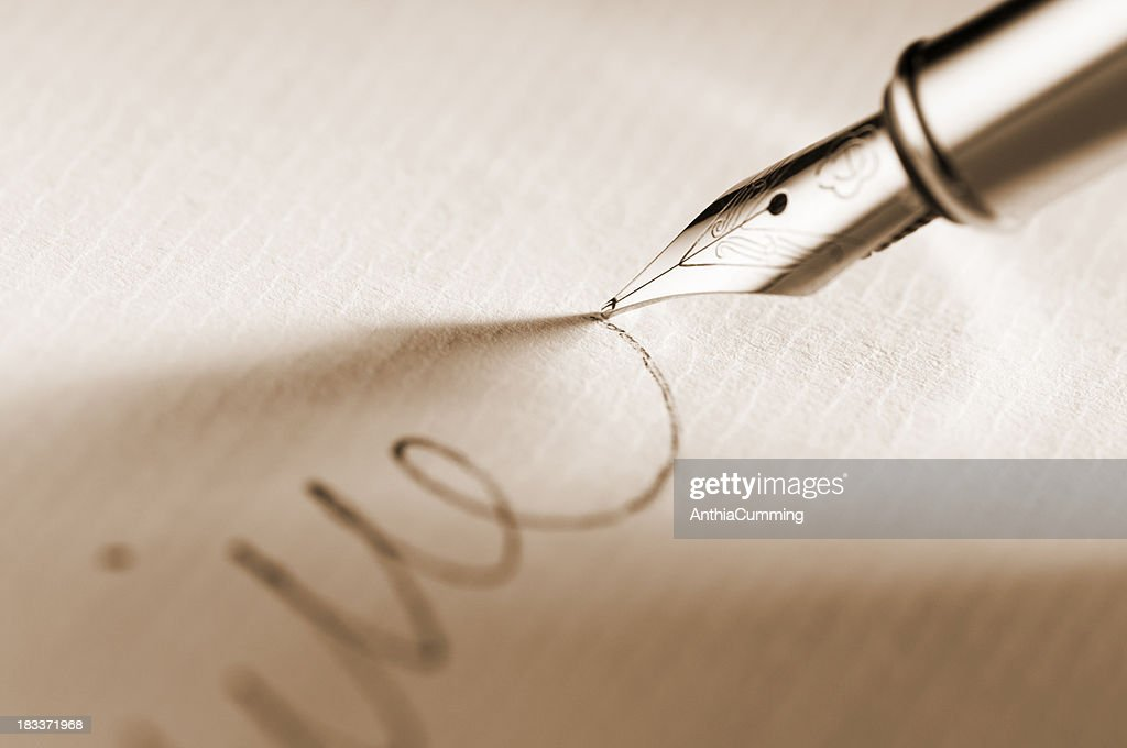 Fountain pen signing a signature on paperwork : Stock Photo