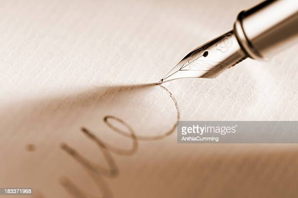 Fountain pen signing a signature on paperwork
