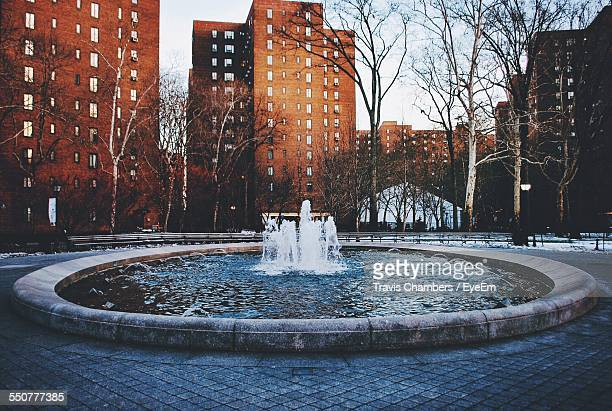 fountain with apartment building in background - fountain stock pictures, royalty-free photos & images