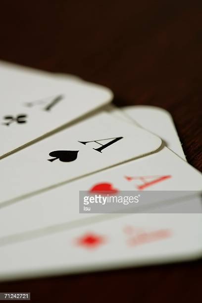 Four aces on a wooden underlay, close-up