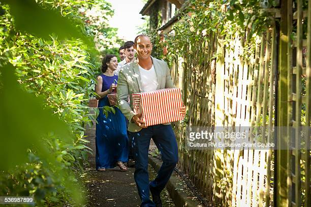 Four adult friends carrying gifts up garden path for surprise party