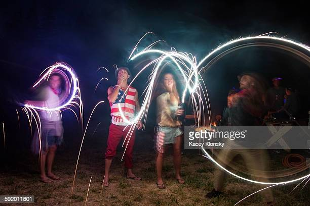 Four adult friends celebrating with sparklers in darkness on Independence Day, USA