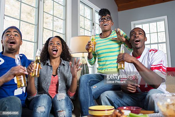 Four adult friends gasping open mouthed whilst watching TV from sofa