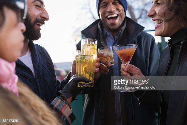 four adult friends laughing and drinking cocktails at recreational bar patio - heshphoto stock pictures, royalty-free photos & images