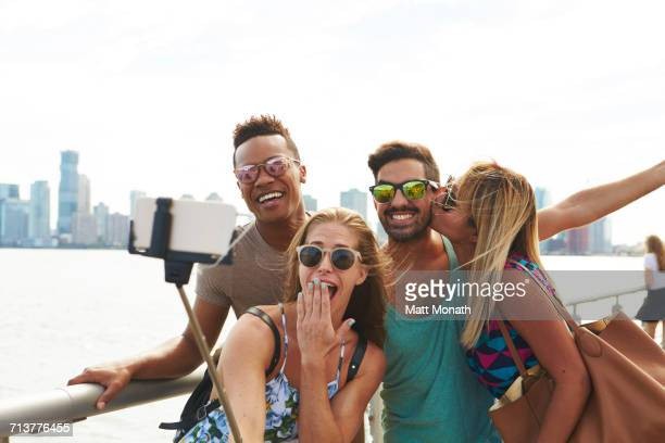 Four adult friends posing for smartphone selfie on waterfront with skyline, New York, USA