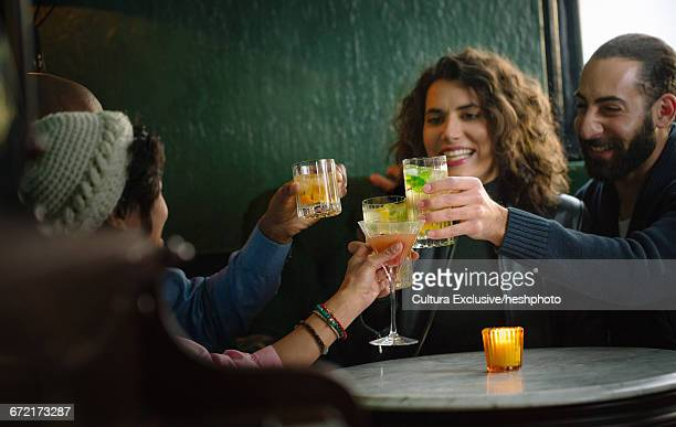 Four adult friends sitting in recreational bar raising a cocktail toast