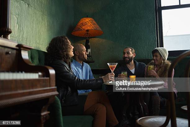 four adult friends sitting in recreational bar socialising - heshphoto stock pictures, royalty-free photos & images