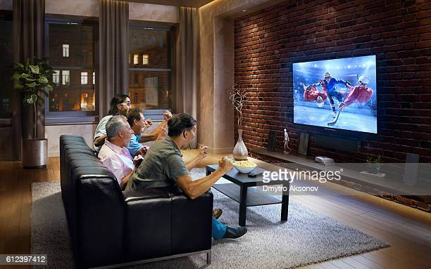 Four adult men watching Ice hockey game on TV